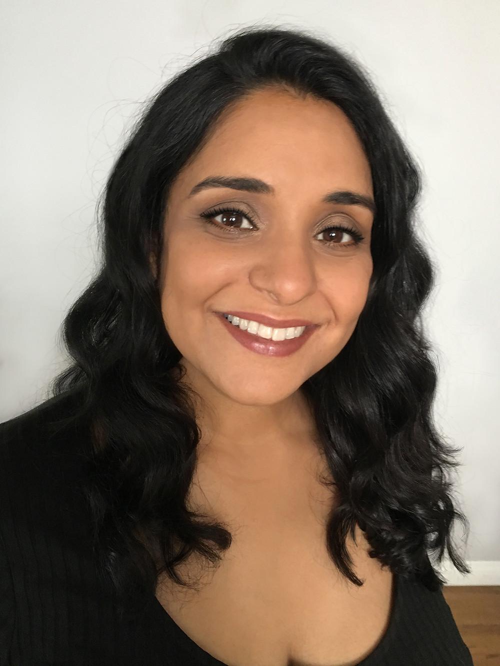Neelanjana Banerjee is looking at the camera and smiling.
