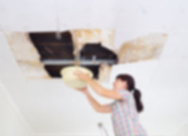 Young Woman Collecting Water In basin From Ceiling.jpg Ceiling panels damaged huge hole in roof from
