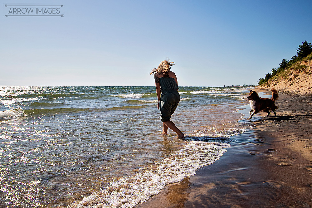 Owner and dog playing at Michigan Dog Friendly Beaches