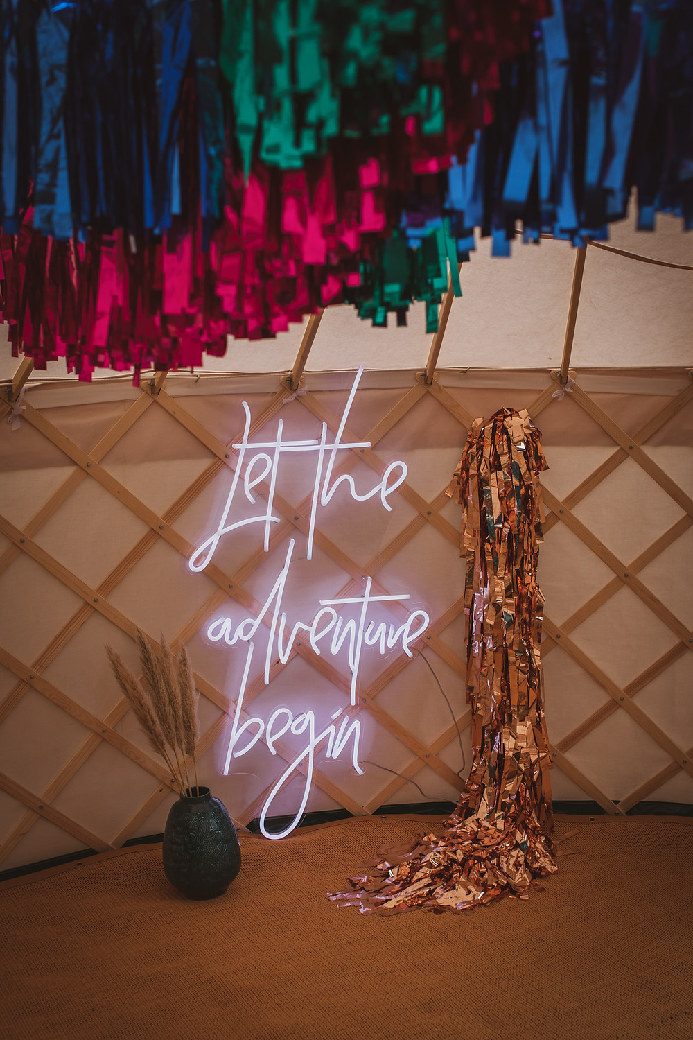Neon 'let the adventure begin' sign with streamers in a yurt