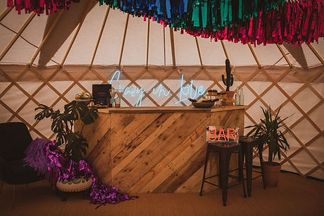 Yurt bar for hire with streamers and neon sign.