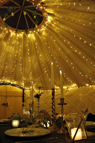 Fairylights and table setting in 18ft yurt Yorkshire