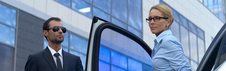 Bodyguard in suit opening car door to fe