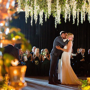 Groom kisses bride under greenery and white flowers, designed by the best wedding planner chicago
