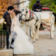 Brid nd Groom kiss by a white horse and carriage planned by Megan Estrada,  Wedding Planner Chicago