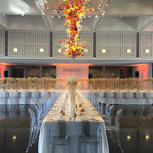 Rehearsal dinner table at Wichita Art Museum. Creative tabl set up unde the chihuly sculpture. Designed by Megan Estrada, North Shore Weddigs & Events a Chicag Wedding Planner