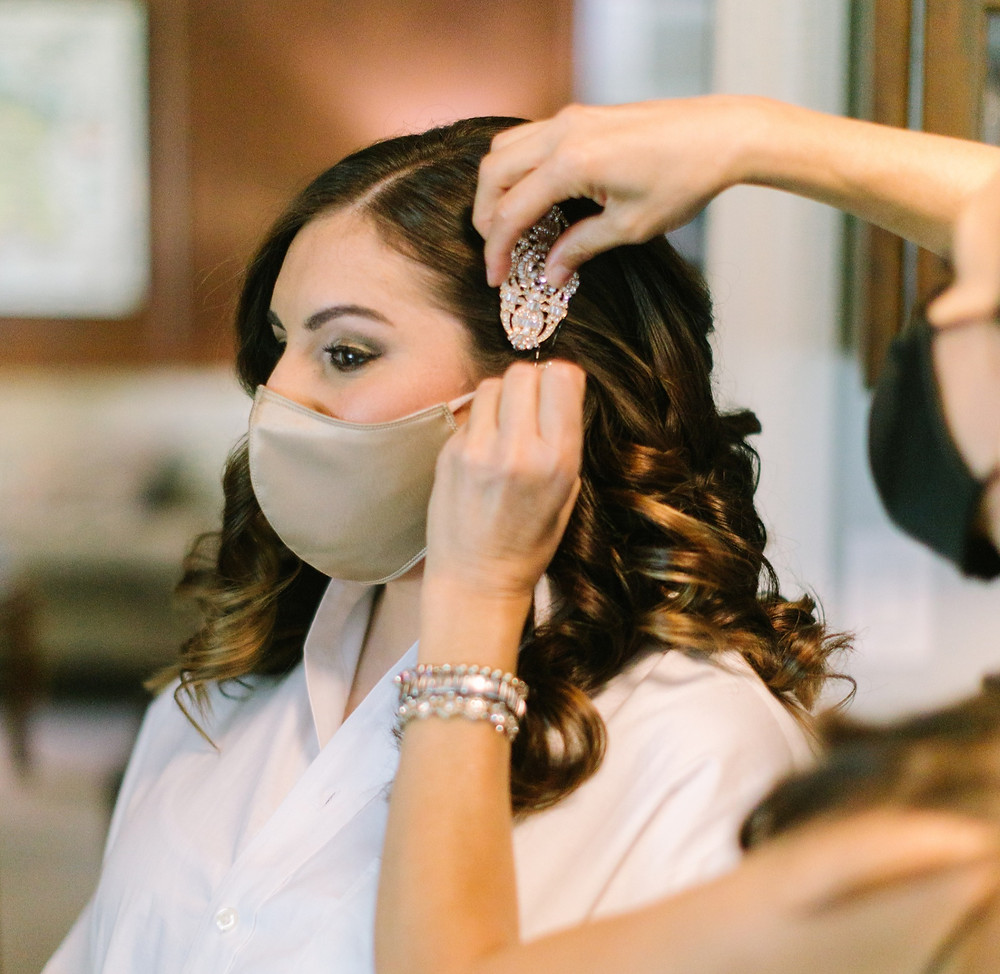 Hairstylist putting hair clip in bride's hair with bride masked.