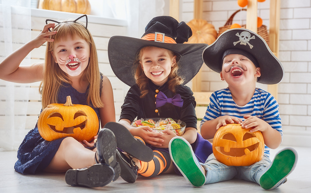 kids laughing and smiling in their cute Halloween costumes with Jack-o-lanterns and Treats