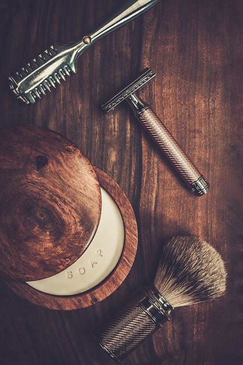 Barber tools, soap, brush and razor on wooden table