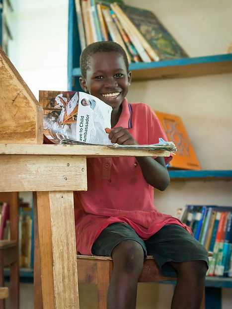 A boy smiles while reading a magazine in Humjibre Library.