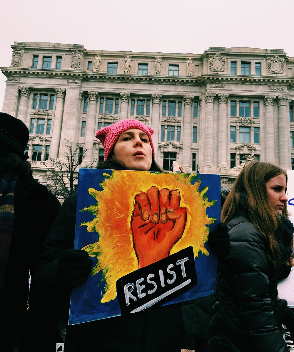 Woman protesting with a pink hat and a signboard showing the word 'resist' and a closed fist