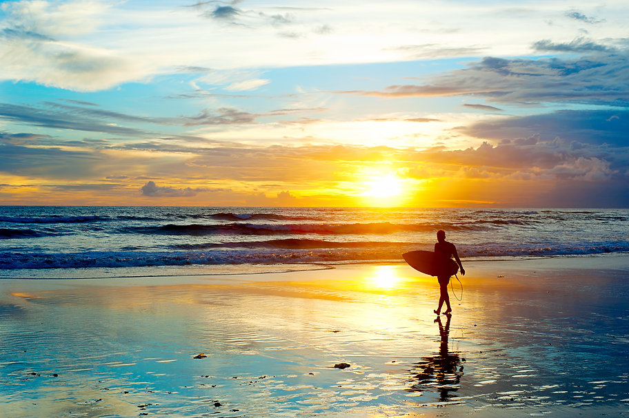 Surfer on the ocean beach at sunset on B