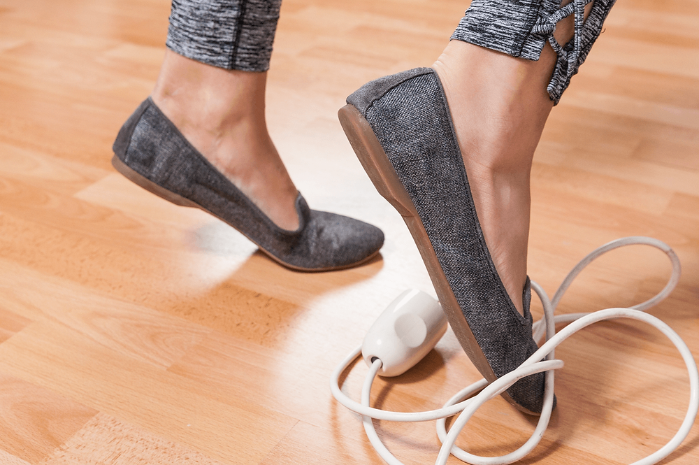 Woman tripping over cord. How to reduce trip hazards in the home.