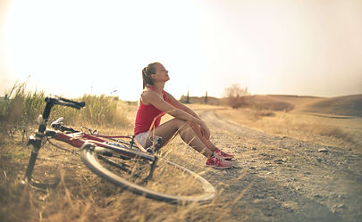 sportive-woman-with-bicycle-resting-on-c