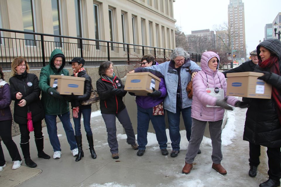 a line of people passing boxes of petitions along