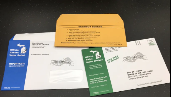 a photo showing the absent voter ballot package - the blue mailing envelop, the green return envelope, and the secrecy sleeve