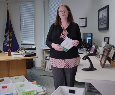 Livonia city clerk Susan Nash is shown in her office holding a returned absent voter ballot. A number of sorting mail containers are arranged on the floor.