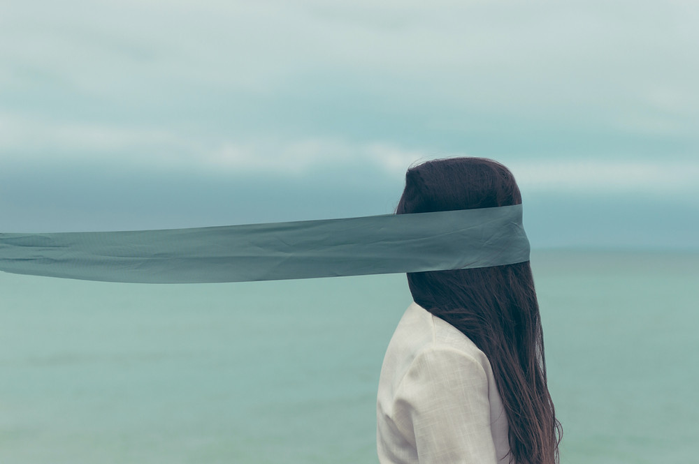 A picture of a girl standing in front of a light blue view of water and the sky. A blindfold is held upon her eyes.