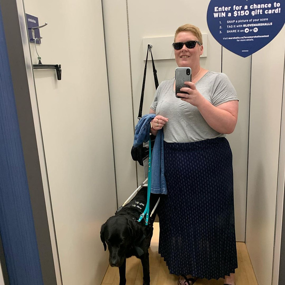 A picture of Ashley and her dog Danson standing in the changing room of a store, taking a photo in the mirror. Ashley wears a dark blue, long skirt and a light grey t-shirt tucked into the skirt. She holds a jeans jacket in her one hand and her phone in the other.