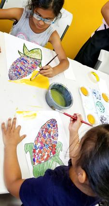 kids painting on a pastel resist