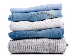 Stack of clothing jeans sweaters on a wh