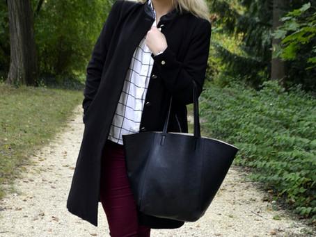 Schwarzer Mantel und rote Jeans