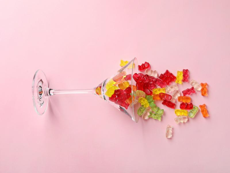 Martini glass with gummy bears falling from it