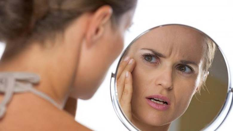 Woman looking at her dull complexion in a makeup mirror