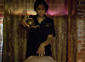 Oil being poured onto massage client