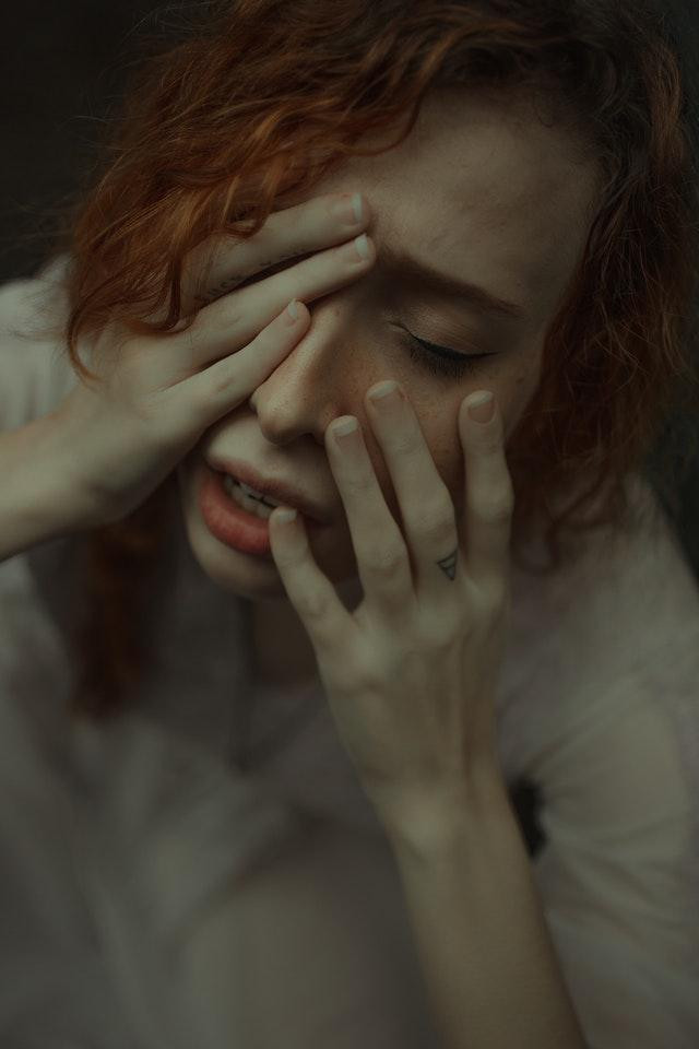 Woman covering her face with her hands, looking stressed