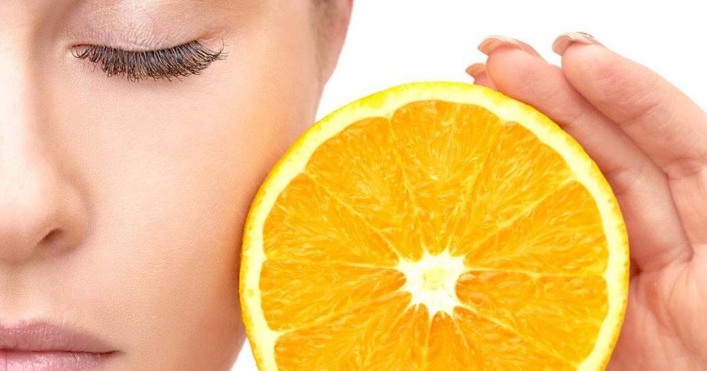 Woman holding orange slice next to her face