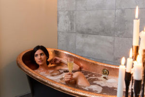 Woman soaking in a copper tub in candellit room with glass of wine