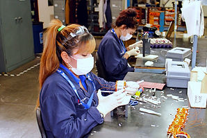 Two Factory Employees Working on Electrical Components