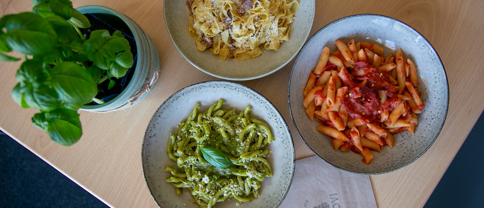 colourful bowls of pasta green, red and white