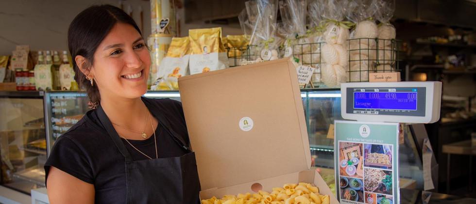 Girl holding pasta box in deli