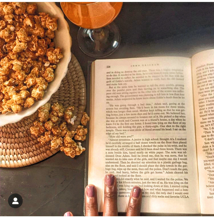 A still life image comprising of a novel,drink and pop corn.