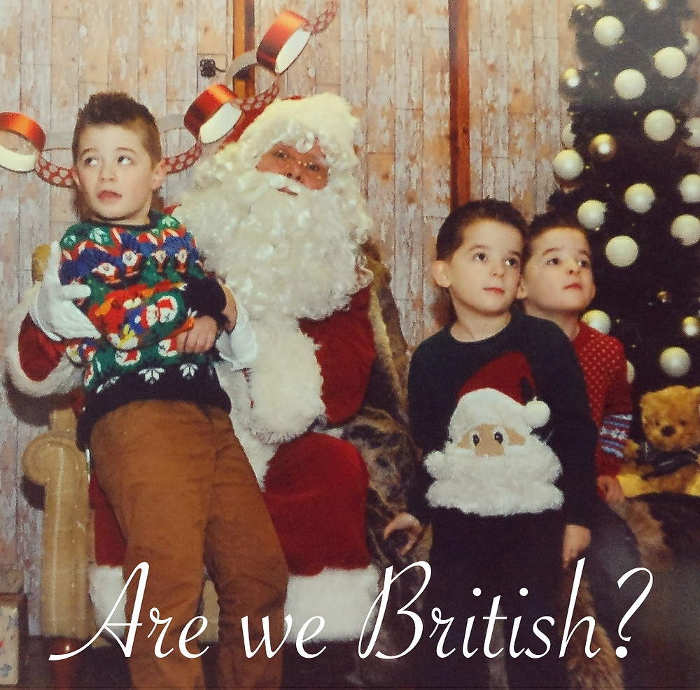 3 adorable boys in Christmas jumpers, all looking in different directions. Santa looking worried and at the camera.