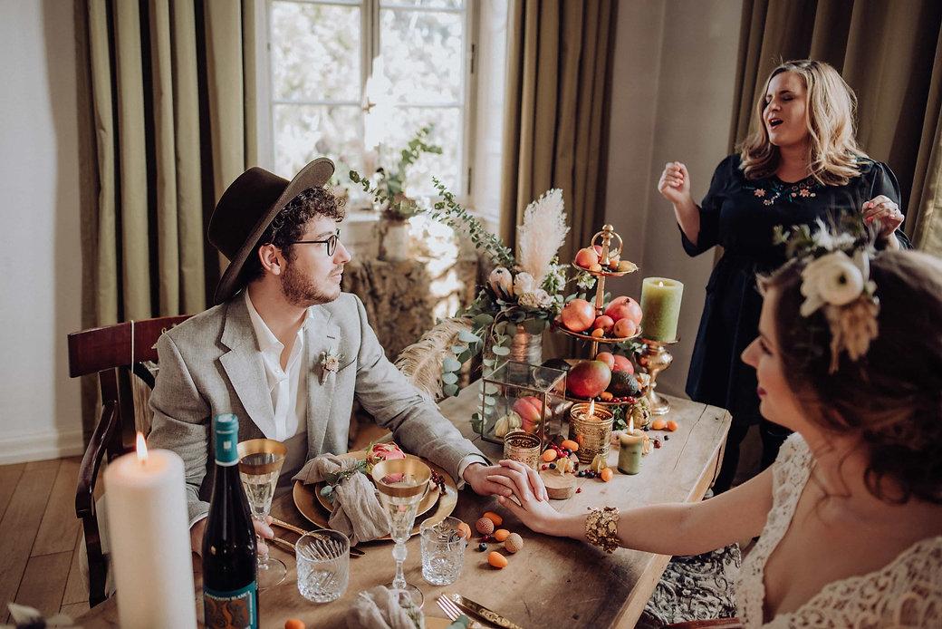 Brautpaar an gedecktem Tisch, Goldtafel, Obst, Nora Brandenburger singt im Hintergrund
