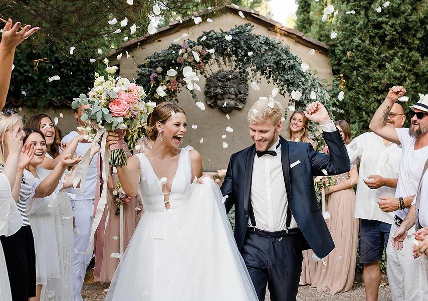 Glückliches Hochzeitspaar nach Trauung, Gäste werfen Blüten