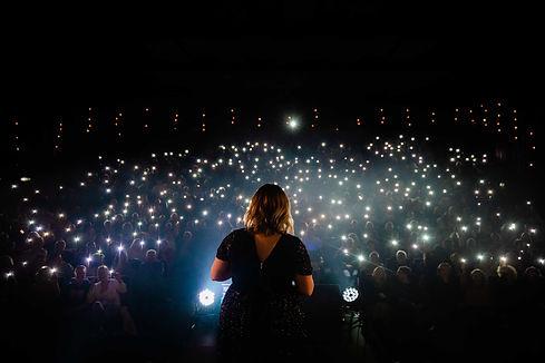 Sängerin Nora Brandenburger steht vor einem großen Publikum, Lichtermeer Zuschauer