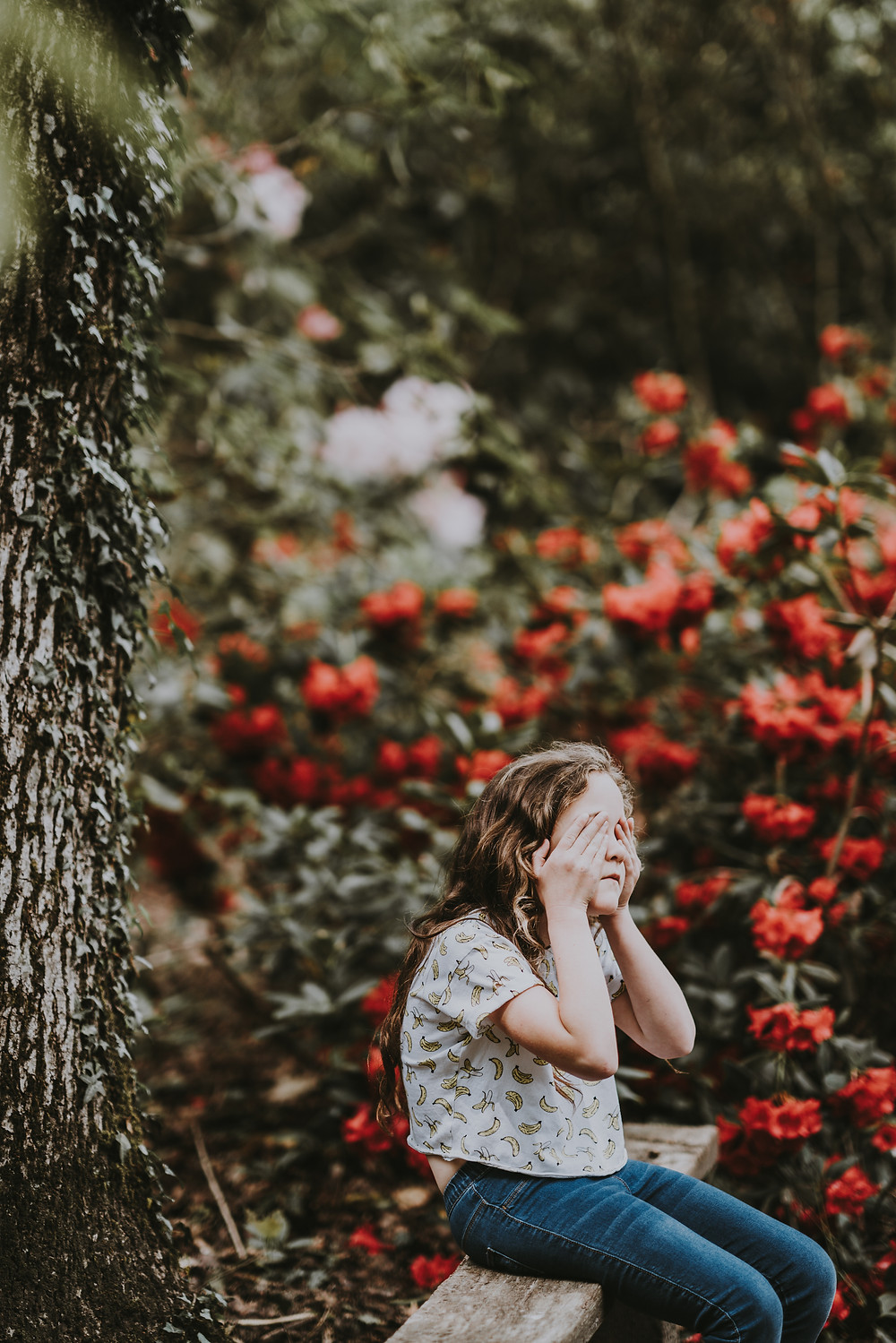 Photo of girl sitting on fence covering her eyes by Annie Spratt on Unsplash