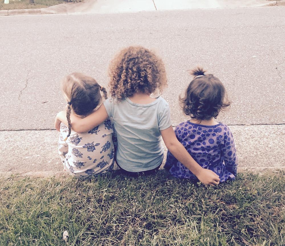 3 girls sitting together. Backs facing camera