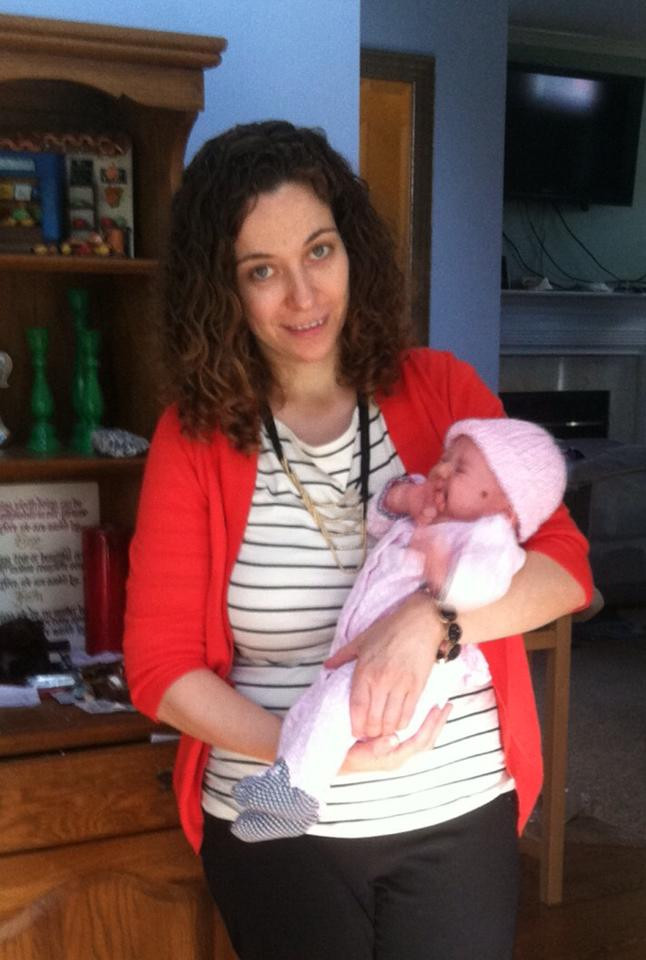 Photo of author holding baby with slanted head.