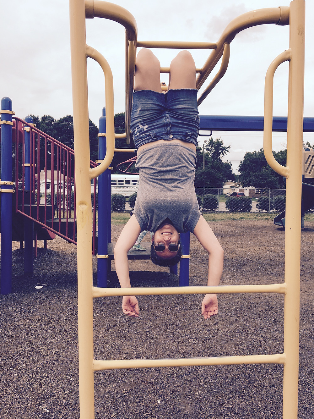 Woman hanging upside down on outdoor jungle gym