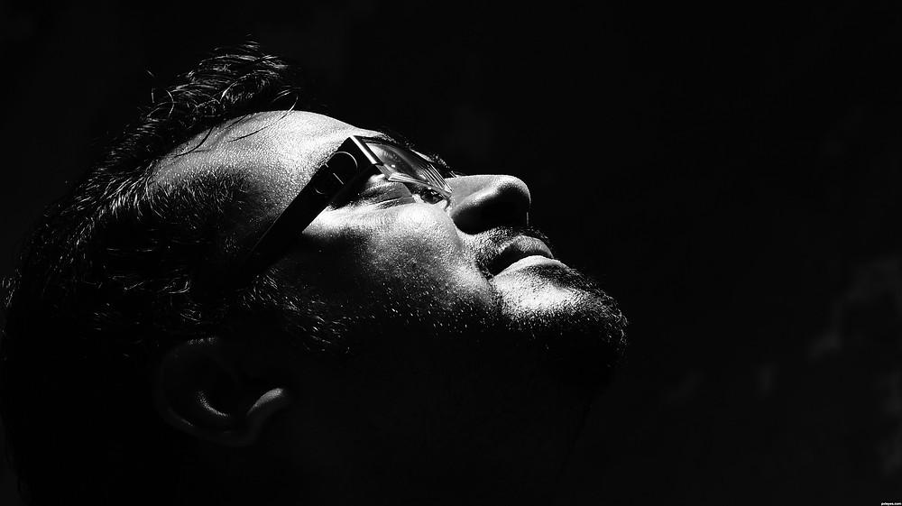 foto em preto e branco de um homem de óculos e olhos fechado com a face para cima como se estivesse em busca de algo