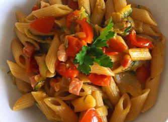 Pennette integrali con pancetta, pomodorini e zucchine