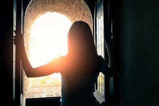 Silhouette of beautiful woman opening wi