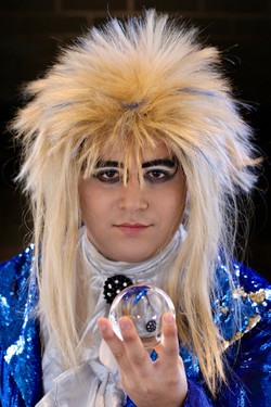 Portrait of a person in cosplay as Jareth the Goblin King from the film Labyrinth. He has a blonde w