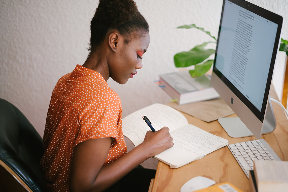 Girl in a bright orange top sitting in front of a computer and writing in a notebook