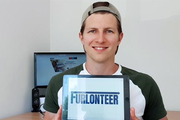 A man holding a Furlonteer sign